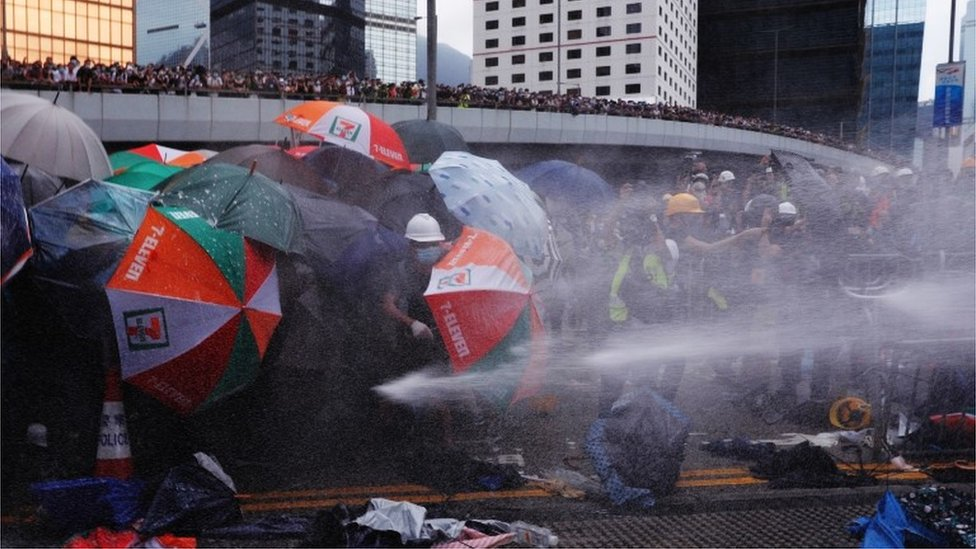 Pemrotes melindungi diri dengan payung