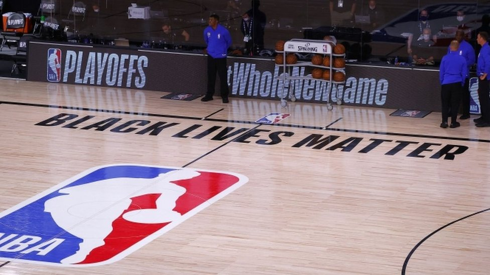 Referees on an empty court after the Milwaukee Bucks boycott an NBA play-off game