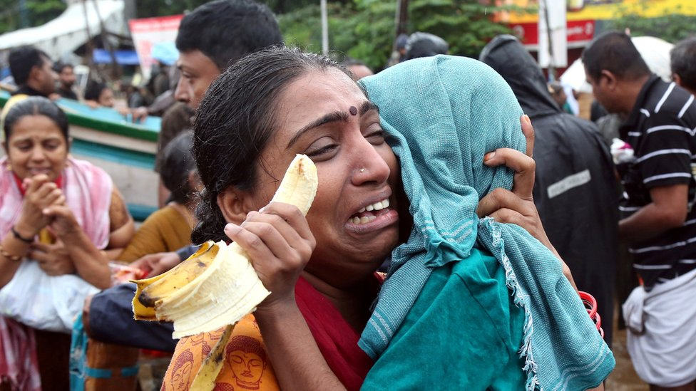 A woman cries as she holds her son after they were evacuated from a flooded area in Aluva - 18 August