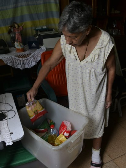 Norma Mújica shows the staples that come with the government good box