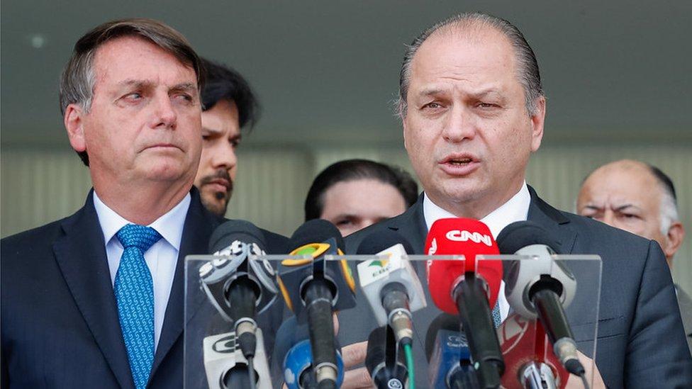 Bolsonaro olha seriamente para Barros, que fala diante de microfones de jornalistas