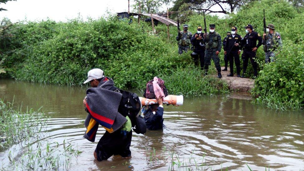 Venezolanos cruzando un río.
