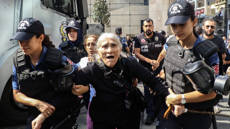 An elderly female demonstrator is detained by police