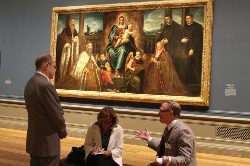 "Exhibition co-curators Frederick Ilchman (R) and Robert Echols (L) speak with a visitor in front of Jacopo Tintoretto""s ""Doge Alvise Mocenigo and Family before the Virgin and Child"""