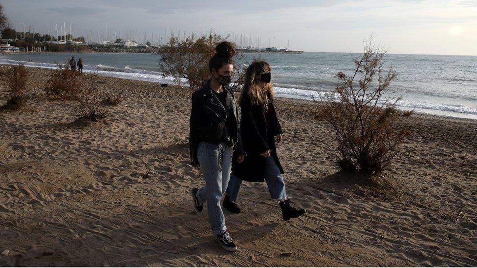 Люди в защитных масках гуляют по пляжу в необычно теплый день в Афинах