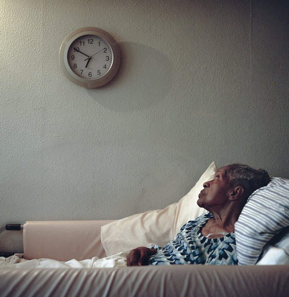 An elderly lady lying in bed looking at a wall clock