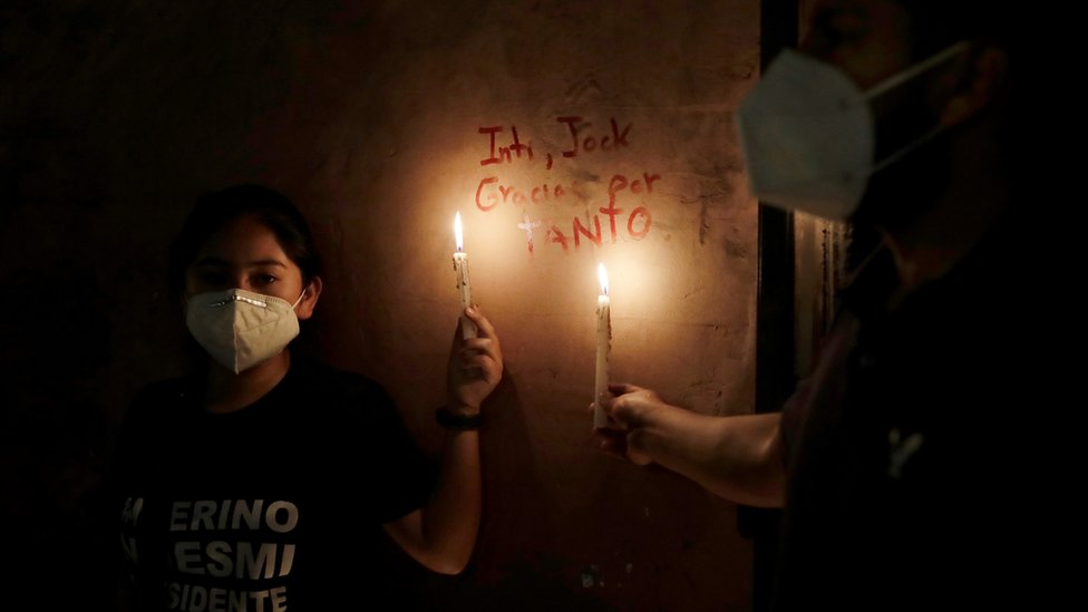 "Women hold candles next to the names of two people who were killed in clashes during protests following the ouster of President Martin Vizcarra, in Lima, Peru November 15, 2020. The writing reads ""Inti, Jack, thank you for so much"""