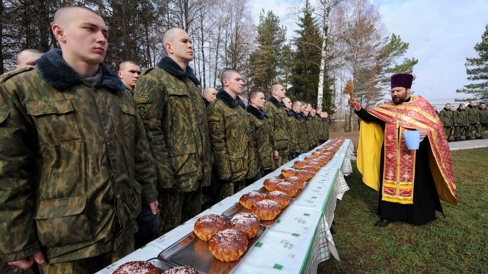 A priest blesses easter cakes and Belarusian soldiers during an Orthodox Easter ceremony