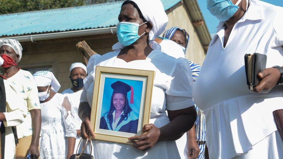 ग्रेस लुगालिकी (द्वितीय आर) ने अपनी बेटी डॉ। डोरेन लुगालिकी, 39, केन्याई के कोवाल्व में पहली बेटी, जो 13 जुलाई, 2020 को पश्चिमी केन्या में अपनी बेटी के अंतिम संस्कार के दौरान सीओआरआईडी -19 कोरोनोवायरस की मृत्यु हो गई थी, का चित्र रखती है।