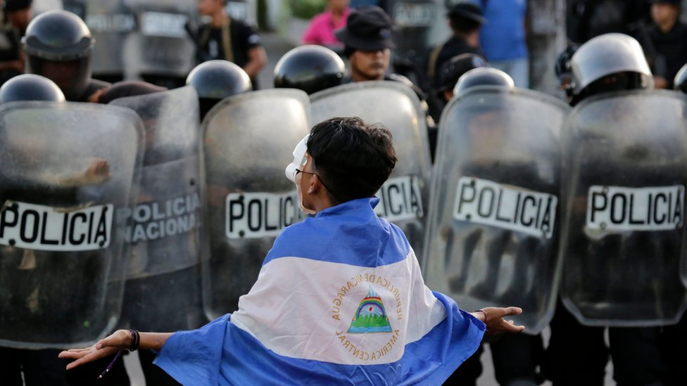 A masked youngster protests against Nicaraguan President Daniel Ortega's government in front of a line of riot police blocking a street in Managua, on September 13, 2018