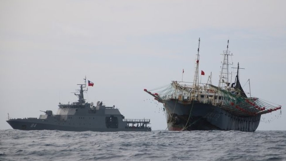 "One vessel, part of a fleet of hundreds of Chinese fishing boats, sails next to a Chilean Navy ship in Pacific Ocean international waters near Chile""s exclusive economic maritime zone, off the coast of Arica and Parinacota November 30, 2020."