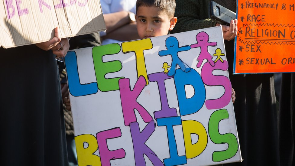 "Child holding banner saying ""Let kids be kids"""