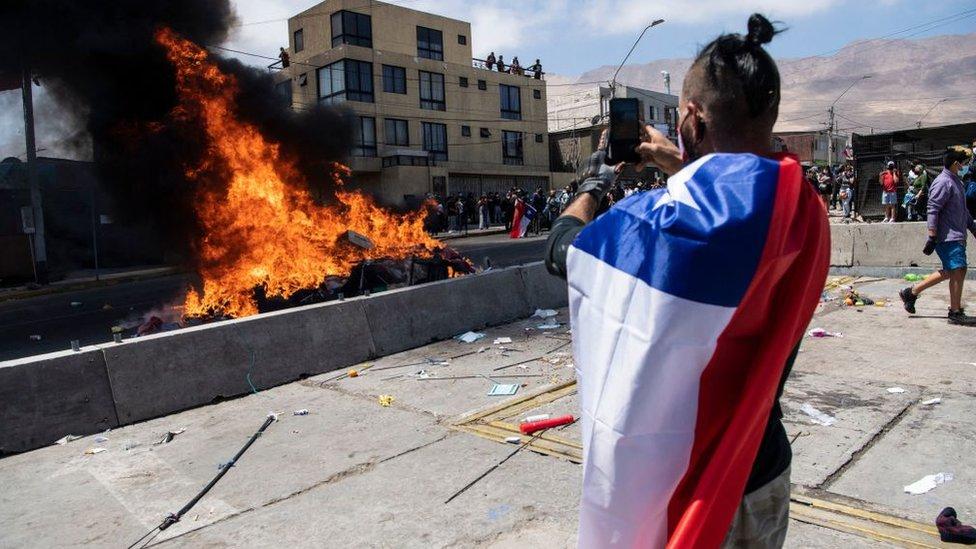 Hombre con la bandera de chile quemando ropa de migrantes