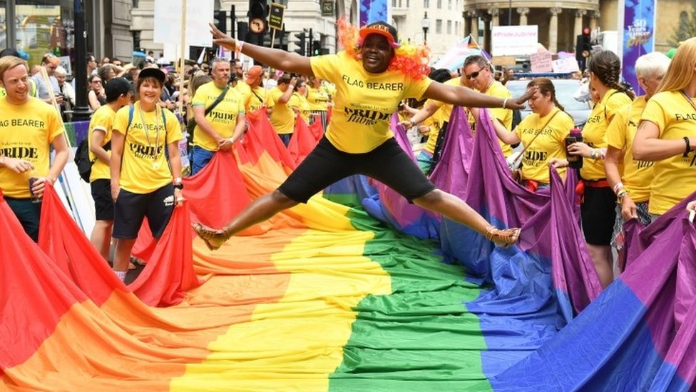 Flag bearer jumps over a rainbow flag at London's Pride event