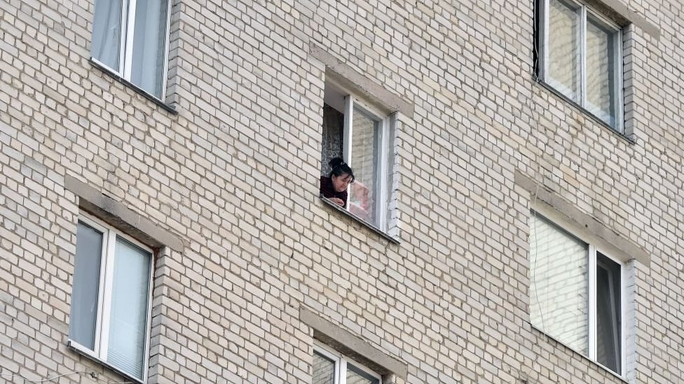 Woman at the window in a block of flats in Ukraine