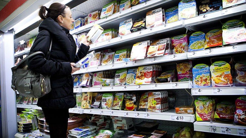 Mujer chequeando los ingredientes de un producto.