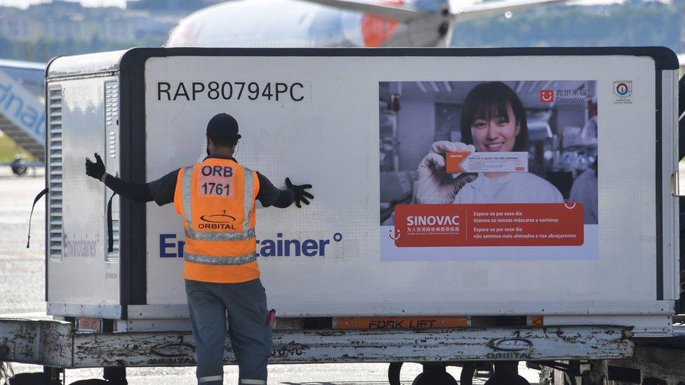 巴西聖保羅瓜魯柳斯國際機場停機坪上地勤人員卸載剛空運抵達的中國科興克爾來福疫苗(18/12/2020)