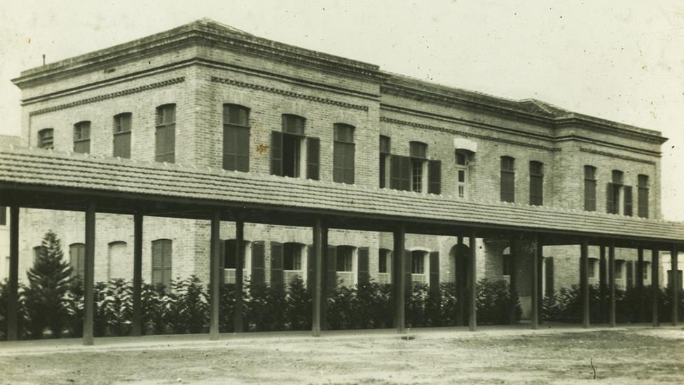 Foto em preto e branco mostra fachada de prédio