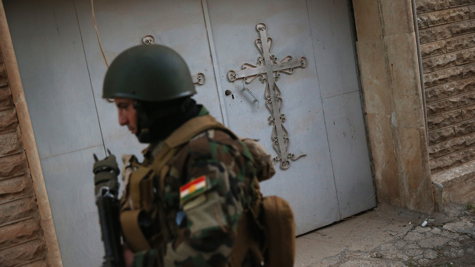 A Christian militiaman patrols through the abandoned Assyrian streets of Telskuf on 4 November, 2015 near the frontline with ISIS fighters in Telskuf, northern Iraq.