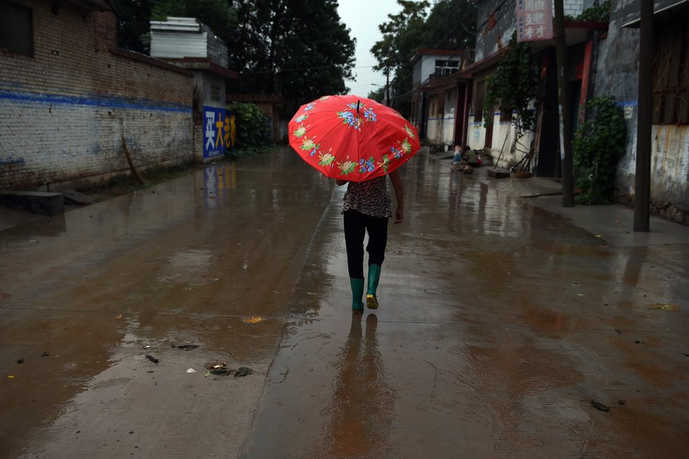 A woman walks down the main street in Weijian village, in China's Henan province on 29 July 2014