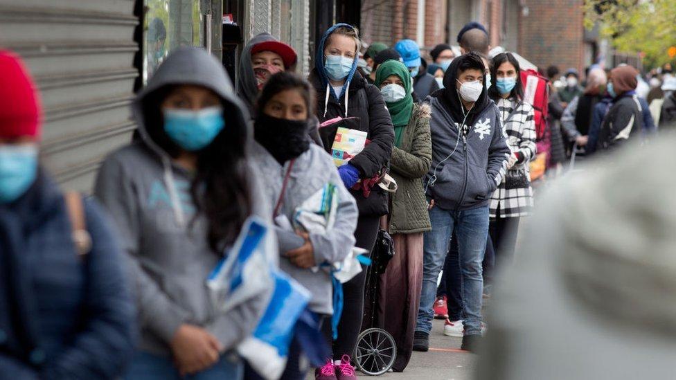 Personas haciendo fila para conseguir alimentos.