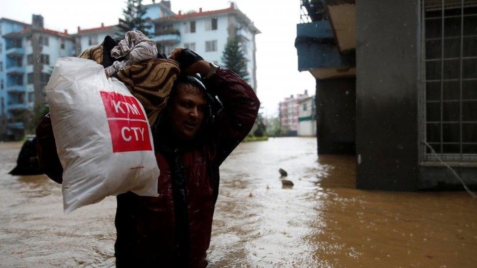 A man carries his belongings towards dry ground in Kathmandu