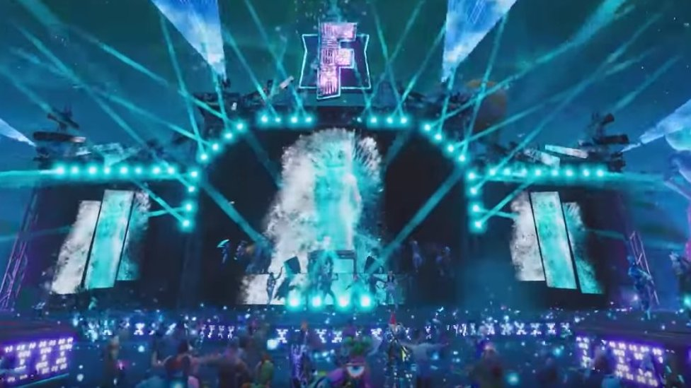 A virtual stage with lights, pyrotechnics, and holograms. Marshmello - a DJ with a large marshmello on his head - is playing the stage.