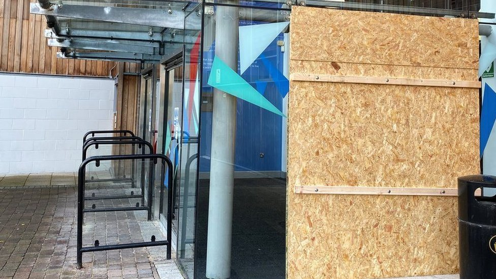 A wooden panel covers a broken window at the Warrington Peace centre