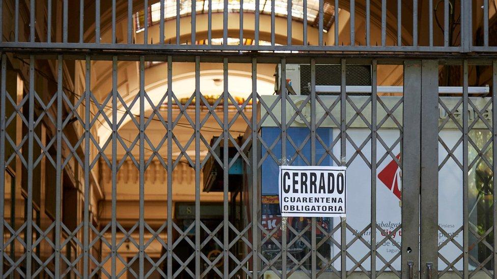 """Rejas en un comercio en Argentina con una placa que dice """"Cerrado, cuarentena obligatoria"""""""