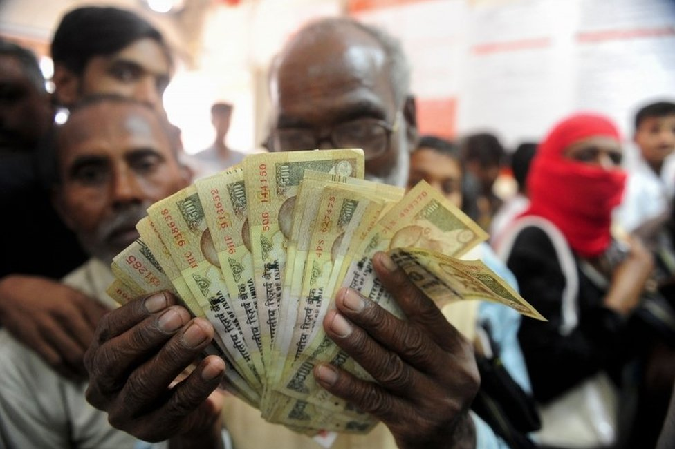 An Indian man holds up old versions of the 500 rupee denomination note as people queue inside a bank to deposit 500 and 1000 Indian rupee notes in Rahimapur village on the outskirts of Allahabad on November 10, 2016