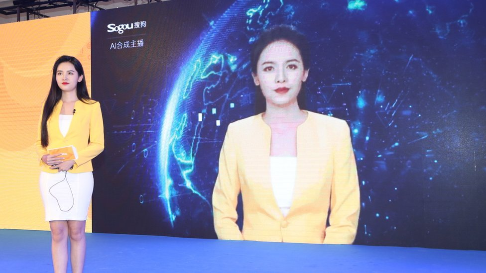 A woman stands in front of a screen with a likeness of her image on stage