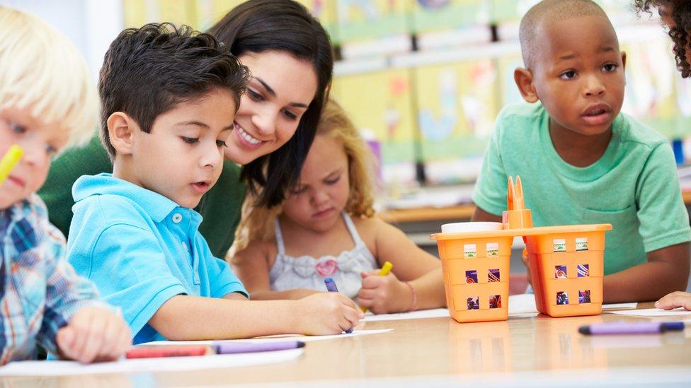 Teacher helping children to draw