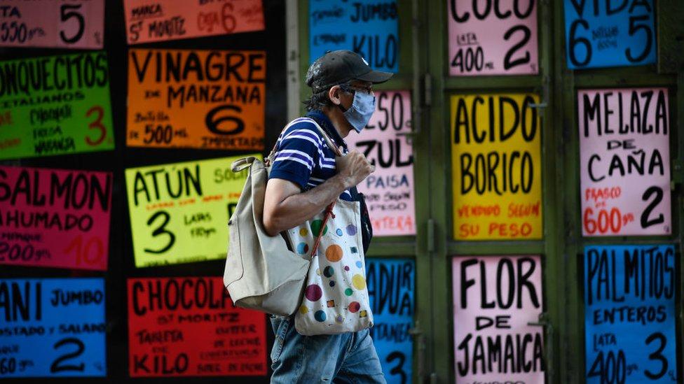 Un hombre camina frente a un comercio de alimentos en Venezuela.