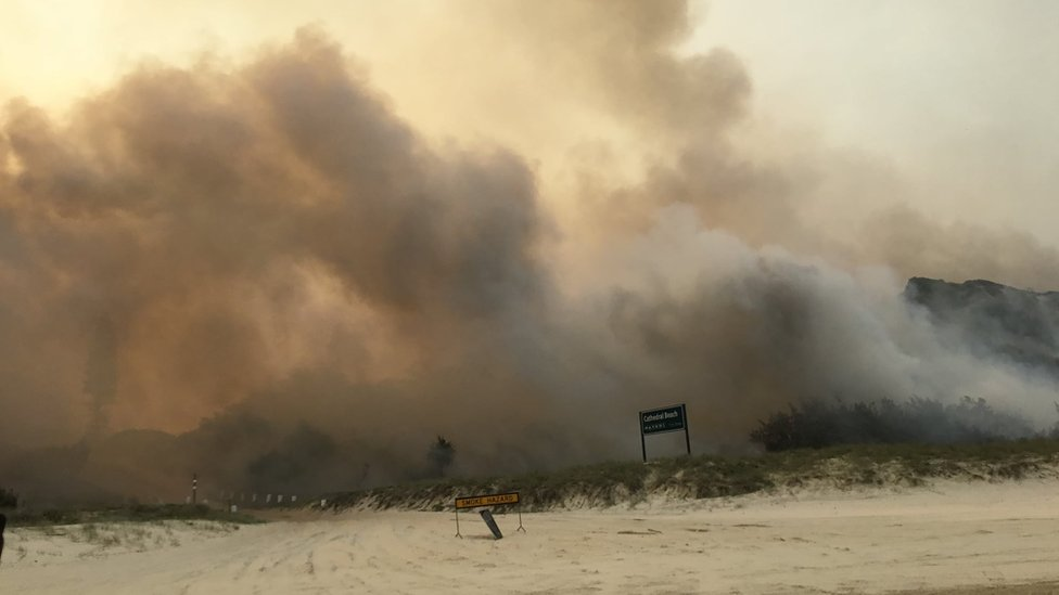Smoke from a massive bushfire on Fraser Island seen at Cathedral Beach on 6 December 2020