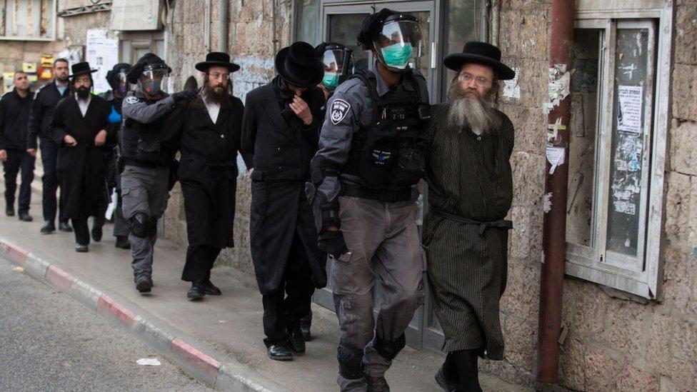 Policías detienen a hombres ultraortodoxos.