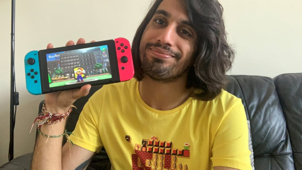 Vaneet wearing a Nintendo t-shirt and holding a Nintendo Switch