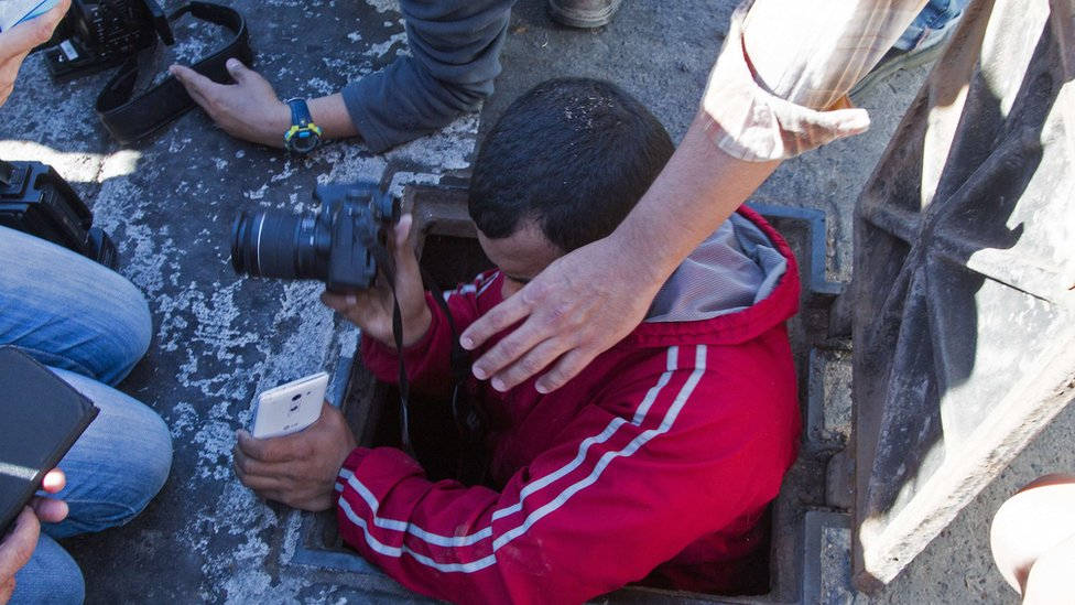 """A journalist enters a manhole of the sewer system through which drug kingpin Joaquin """"El Chapo"""" Guzman tried to escape"""