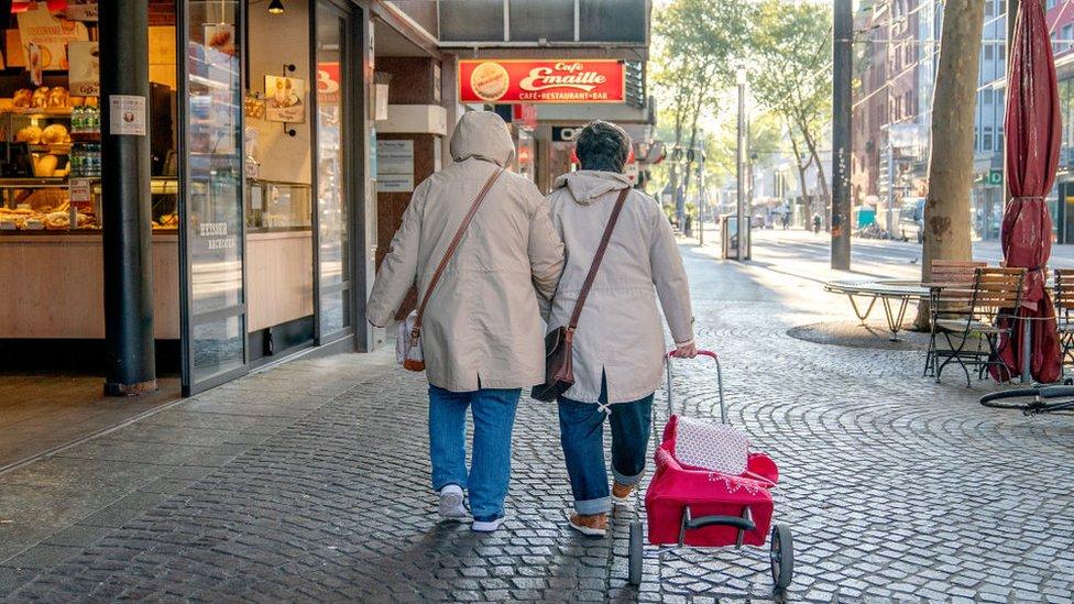 Una pareja camina en una calle en Alemania.