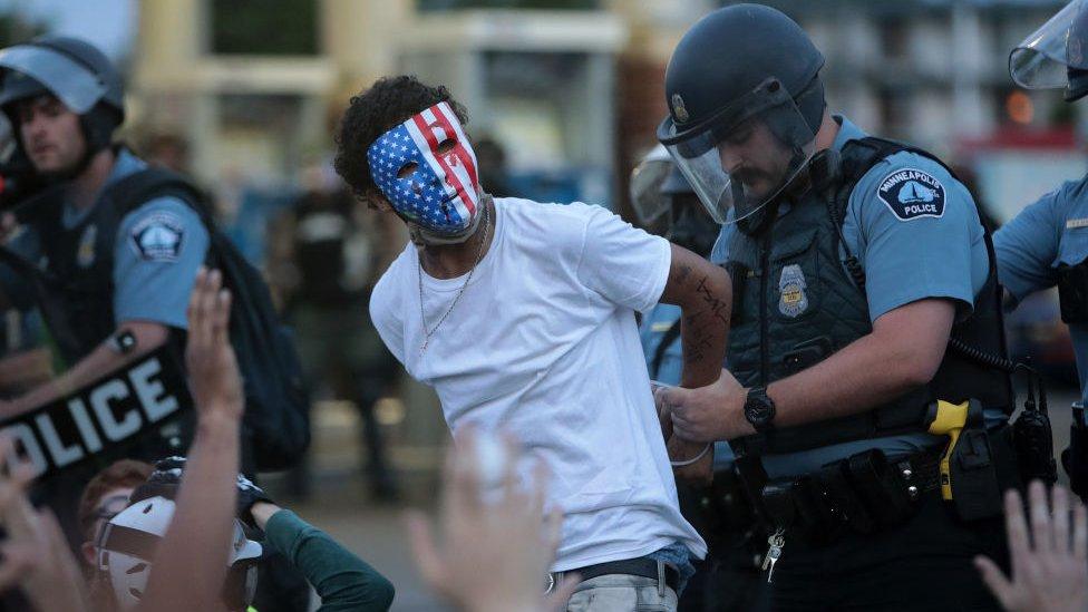 un manifestante es esposado por un agente blanco el 31 de mayo de 2020.