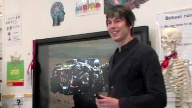 Brian Cox talks in classroom in front of AV screen