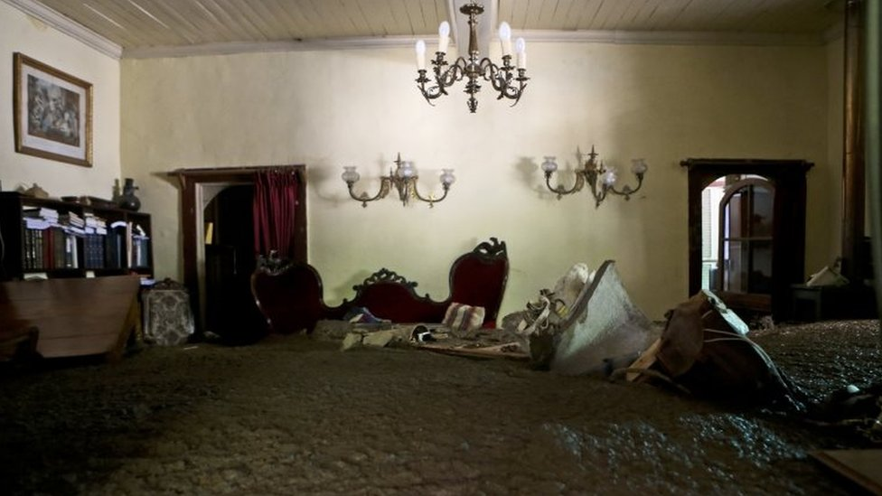 Sludge fills a living room after the overflowing of the Estero San Jose River in San Alfonso, Santiago, Chile, Sunday, Feb. 26, 2017