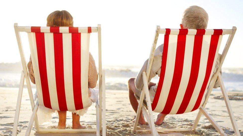 Retired couple sitting in deckchairs