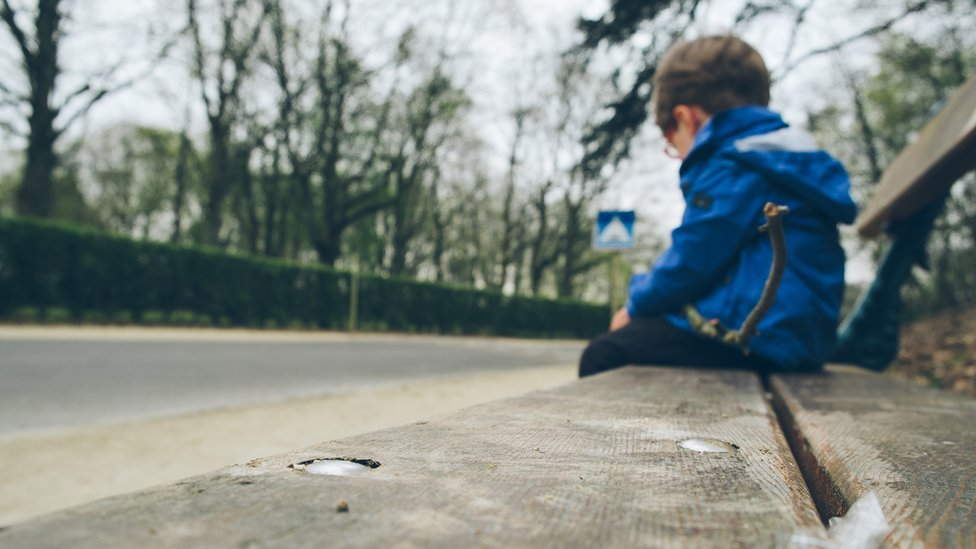 Child sitting on public bench (generic)