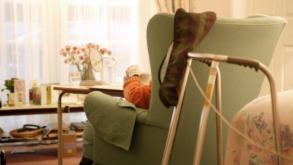 A woman sitting in an armchair inside a care home