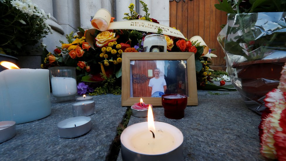 A picture of Vincent Loques, sexton of the Notre Dame church, one of the victims of a deadly knife attack, is seen with candles and flowers in front of the Notre Dame church in Nice, France, October 30, 2020.