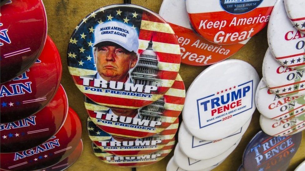Campaign buttons are displayed for sale before US President Donald J. Trump