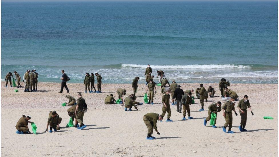 جنود إسرائيليون ينظفون شاطئا ملوثا