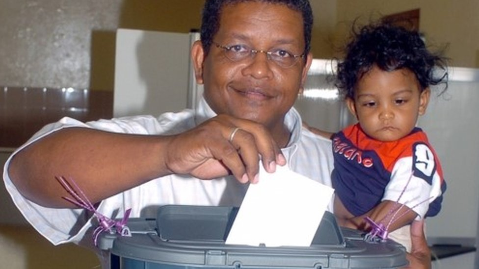 Wavel Ramkalawan casts his vote as he holds his nine-month-old son Amos at a polling station in St. Louise constituency, Seychelles, July 30, 2006