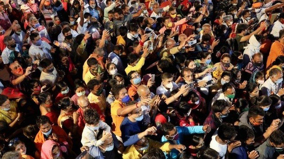 Devotos fazem oração em meio à multidão durante festival
