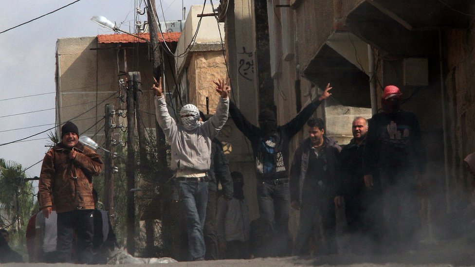 Anti-government protesters gesture as they gather on the streets of Deraa on 23 March 2011